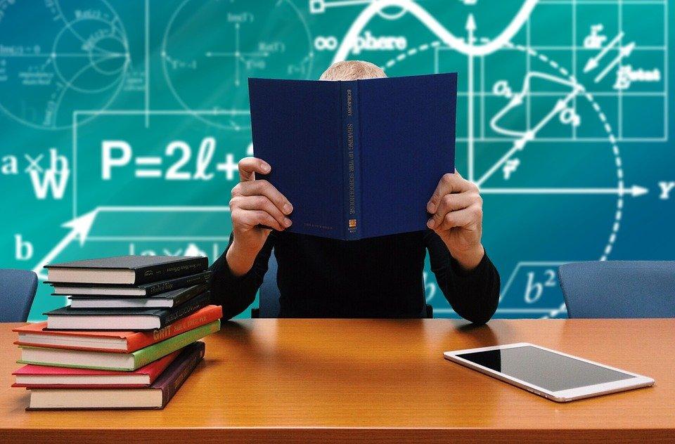 本を手に分析と学習をする人