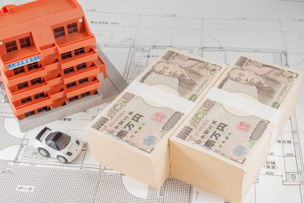 1万円の札束とマンションと車の模型