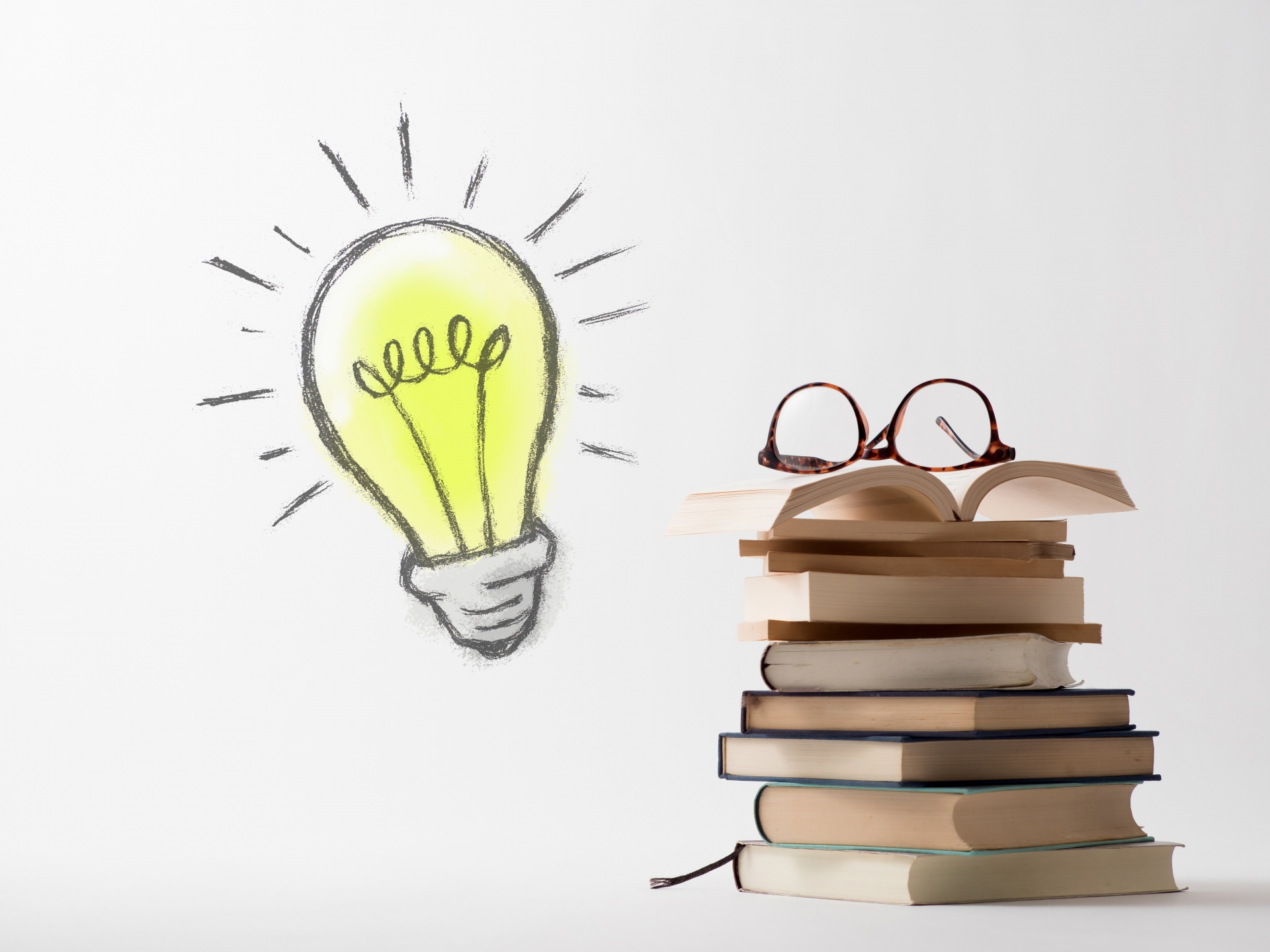 電球の絵と本とメガネ