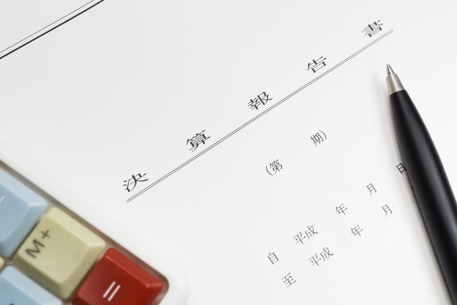 決算書報告書とペンと電卓