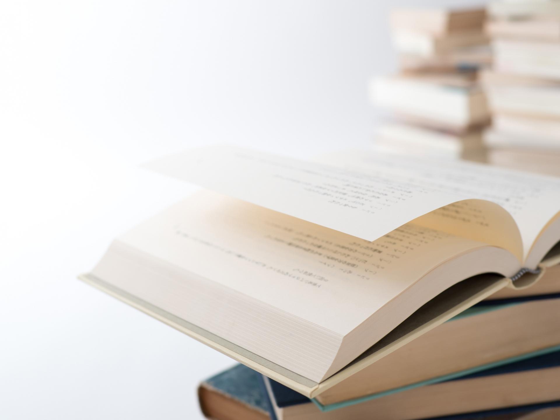 重ねられた本の上で開かれている本